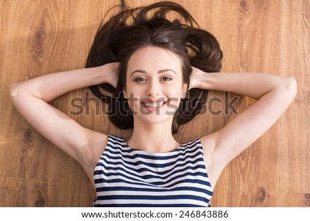 Top view of young woman is lying on the floor and looking at camera. - stock photo
