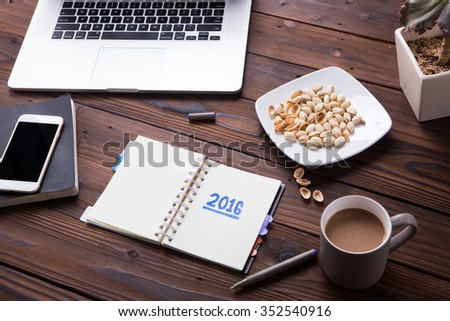 Top view office desk mockup: laptop, notebook, smartphone, snack pistachios, flower, and cup of coffee on rustic brown wooden background. New year 2016 resolution - stock photo