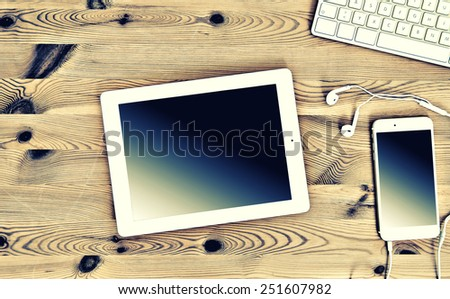 Top View Office Workplace with Keyboard, Tablet PC, Phone. Vintage Instagram style toned picture - stock photo