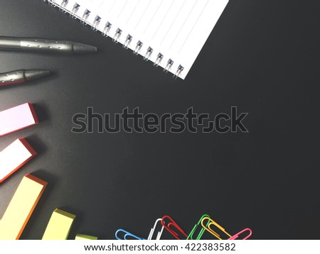 Top view on blank sheet of paper, sticky notes, and pen on black office desk, business concept - stock photo