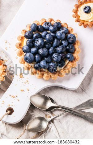 Top view on blueberry mini tart served on white cutting board with vintage teaspoons. - stock photo