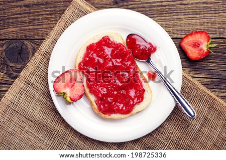 Top view on bread with strawberry jam on wooden table - stock photo