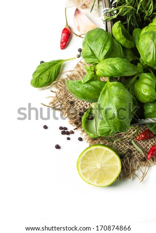 Top view on bunch of fresh herbs basil and rosemary with peppers and lime on sackcloth over white - stock photo