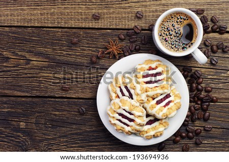 Top view on cup of coffee and cookies on wooden table - stock photo