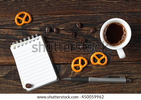 Top view on cup of coffee and notepad on a wooden table. Space for your text