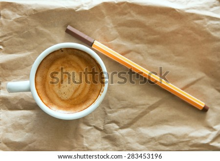 Top view on delicious breakfast cup of strong aroma espresso coffee with color pencils and watercolor paper notepad on a recyclable brown paper and white table, copy space, vintage toning - stock photo