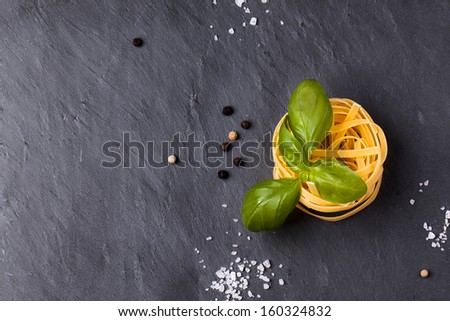 Top view on dry pasta and fresh basil served with sea salt on dark gray background - stock photo