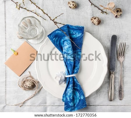 Top view on easter table setting with vintage silverware, white plate, blue textile napkin, quail eggs and blossom branch served on gray tablecloth - stock photo