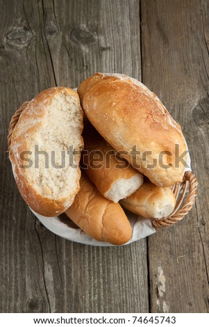 Top view on fresh bread in basket on old wooden table - stock photo