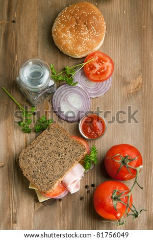 Top view on fresh sandwich with ham, tomatoes, sliced onion, burger's bun and ketchup on old wooden table - stock photo