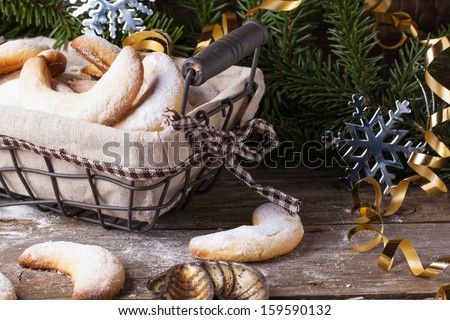 Top view on homemade sugar cookies crescent served in basket with vintage cookie-cutters and gifts near christmas tree over vintage teatured background - stock photo