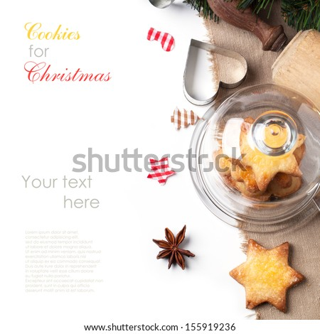Top view on homemade sugar cookies served in glass tray with cap with anise and metal cookie cutters over white with sample text - stock photo