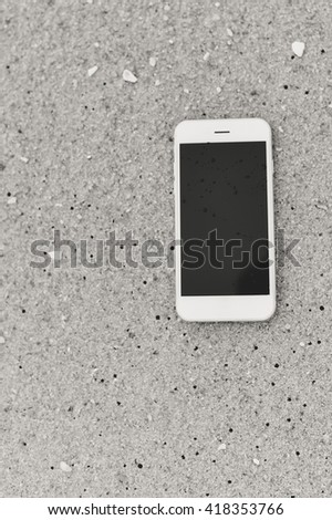 Top view on mobile phone on sandy summer beach background. Happy joyful vacation close up  - stock photo