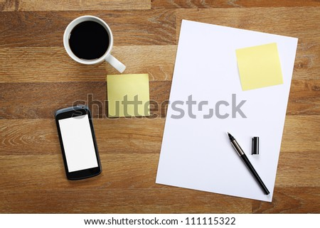 Top view on paper, pen, cup of coffee, sticky notes and smartphone on wooden office desk. - stock photo