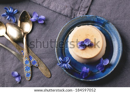 Top view on plate with caramel pannacotta served with violet flowers and vintage teaspoons over gray textile - stock photo