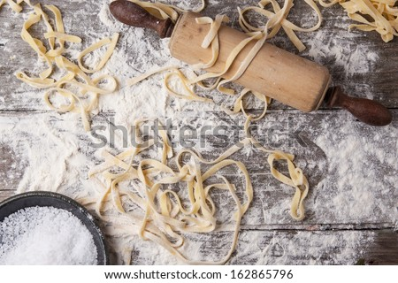 Top view on raw homemade pasta with flour, sea salt and vintage rolling pin over old wooden table - stock photo