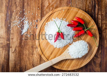 Top view on rice grain and chilli pepper in composition on wooden table