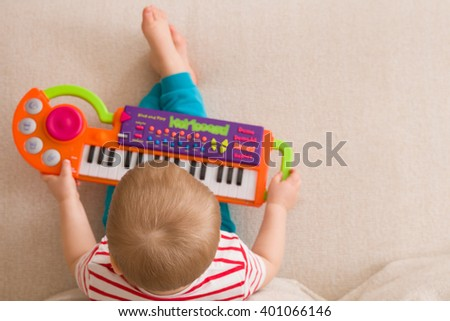 Top view on small cute toddler boy sitting on the sofa and playing on the toy piano. A little boy learning to play piano listening to music. Early development for toddler. Musical education for kids - stock photo