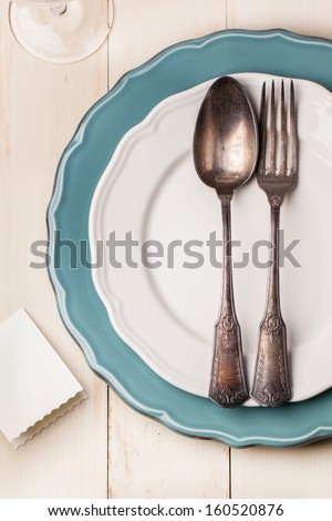 Top view on table setting with vintage silverware on white and turquoise plates with blank guest card on white wooden table - stock photo