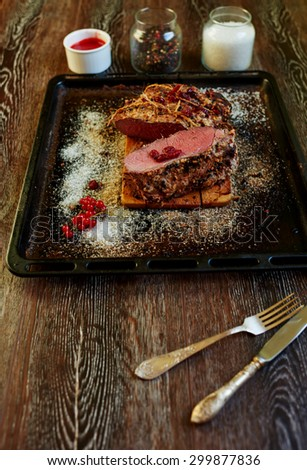 Top view on the table is a pan which is a large piece of lamb, standing beside spicy sauce with the addition of sour wild berries next to a baking tray are silver cutlery - stock photo