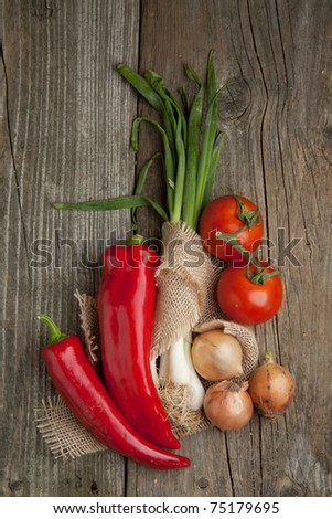 Top view on tomato, onions and paprika on old wooden table - stock photo