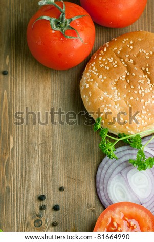 Top view on tow fresh tomatoes, burger's bun and sliced onion on wooden table as background - stock photo
