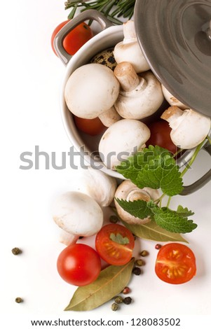 top view on white mushrooms in pan, sliced cherry tomatoes, garlic and herbs over white - stock photo