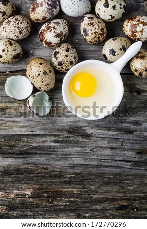 Top view on whole and broken quail eggs and yolk in white bowl over old wooden background - stock photo