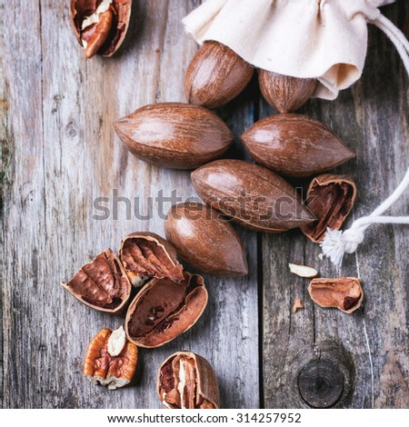 Top view on whole and chopped pecan nuts on old wooden table. Square image
