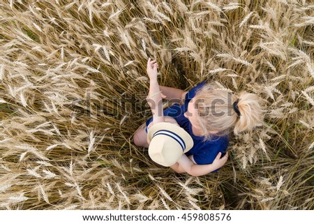 Top view on woman holding adorable toddler boy in her hands and walking in the wheat field on a sunny summer day.  cute child putting on hat to his happy mother. Family lifestyle concept. - stock photo