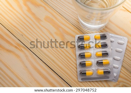 Top view packaging of pills and capsules of medicines and a glass of water placed on a wooden table, warm tone photo. - stock photo