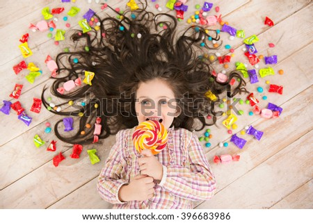 Top view photo of beautiful little girl lying on wooden floor with candies. Girl looking at camera, smiling and holding big round candy - stock photo
