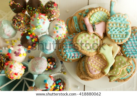 Top view photo of colorful cake pops and easter cookies on table - stock photo