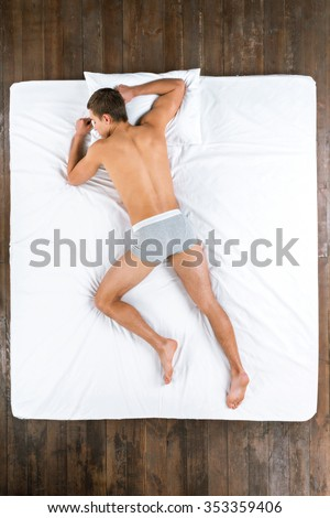 Top view photo of handsome Caucasian man. Young man sleeping on stomach on big white bed and wearing grey underwear - stock photo