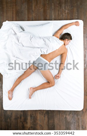 Top view photo of handsome Caucasian man. Young man sleeping on stomach on big white bed under blanket like super man and wearing grey underwear - stock photo