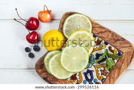 Top view photo of lime and lemon slices, blueberrues and cherry. Summer fruit and berry snack on wooden background. Stilllife photo of fresh raw fruits. - stock photo