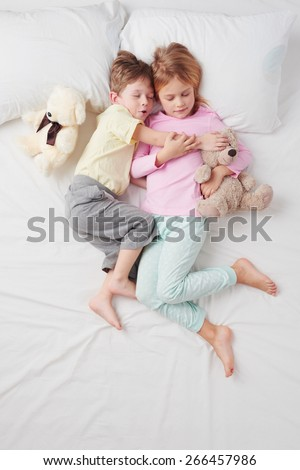 Top view photo of little brother and sister. Children hugging each other. They both sleeping on white bed - stock photo