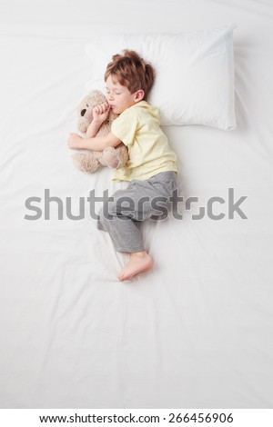 Top view photo of little cute boy sleeping on white bed with teddy bear. Quiet Foetus pose. Concept of sleeping poses - stock photo