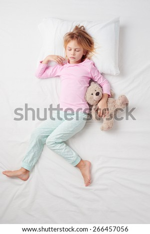 Top view photo of little girl sleeping on white bed with teddy bear. Concept of sleeping poses - stock photo