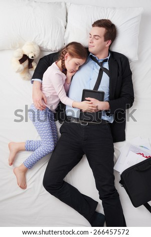 Top view photo of tired businessman wearing suit, and his little cute daughter. Father's arm is over daughter. They both sleeping on and holding tablet computer. Open briefcase and graphics are on bed - stock photo