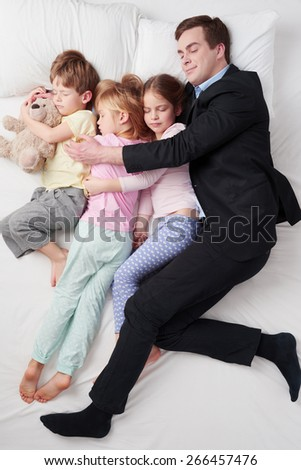 Top view photo of tired businessman wearing suit, and his three children. Father hugging his daughters and son. Children sleeping with father - stock photo