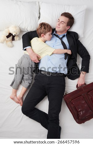 Top view photo of tired businessman wearing suit with briefcase, and his little cute son. Father's arm is over son. They both sleeping on white bed - stock photo