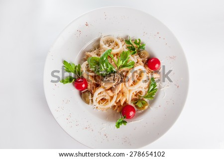 Top view  Plate of Seafood Pasta with squid, mussels with cream, decorated with cherry tomatos, olives, parmesan and herbs on the white plate isolated - stock photo