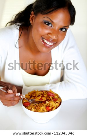Top view portrait of a smiling young woman looking at you and having healthy breakfast at soft colors composition - stock photo