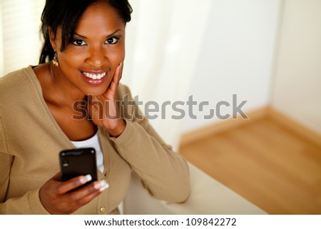 Top view portrait of a young afro-american woman sending a message while smiling at you at home - stock photo