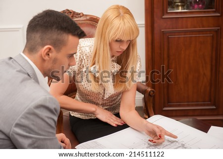 Top view portrait of young beautiful woman client discussing ground plan with handsome architect sitting at the table in design studio,  pointing at architectural plan, creative discussion concept - stock photo