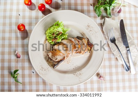 Top view roast sliced chicken fillet on an eggplant garnished with creamy sauce and lettuce on  the white plate on the table with ingredients - stock photo