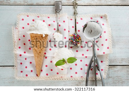 Top view scoop coconut ice cream in waffle cone with utensil, spoon and color rice on wood background. - stock photo