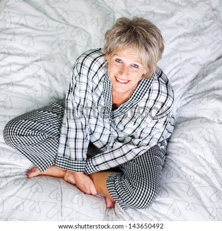 Top view shot of senior female sitting in bed at the living room - stock photo