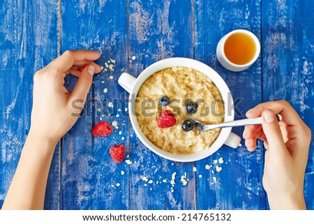 Top view showing hands eating porridge with honey and berries on a blue vintage wooden table - stock photo